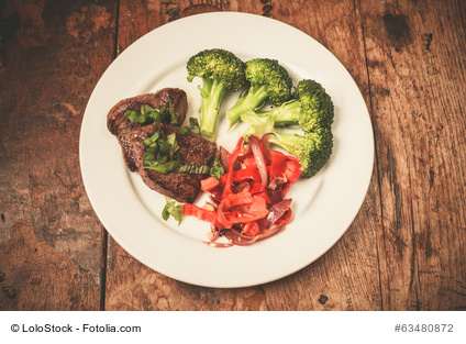 Meat and vegetables including broccoli and red peppers on a plate